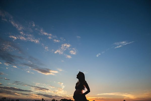 A pregnant woman stands before a sunset with her hands on her belly.