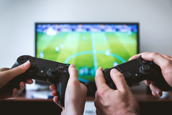 Two pairs of hands hold up video game controllers in front of a TV.