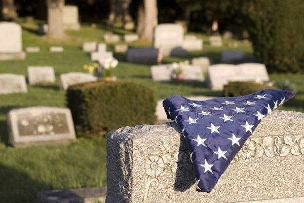 A folded American flag lays on top of a tombstone in a cemetery.