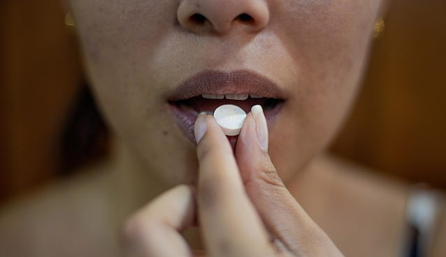 A person holds a white pill up to their mouth.