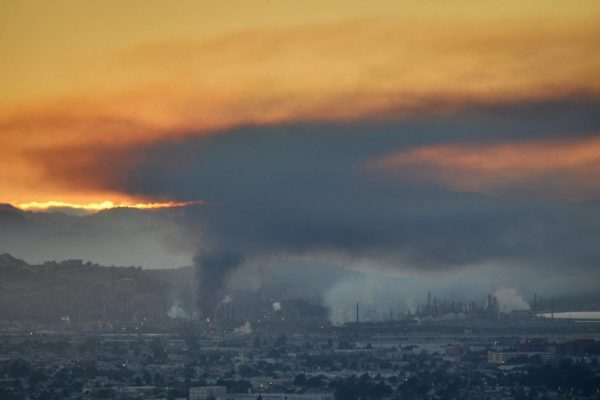 A cloud of pollution rising above a factory and city against a sunset.