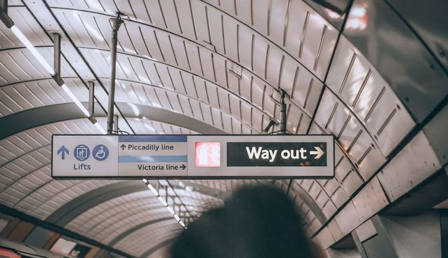"""A crowded subway station with a sign reading """"Way Out""""."""