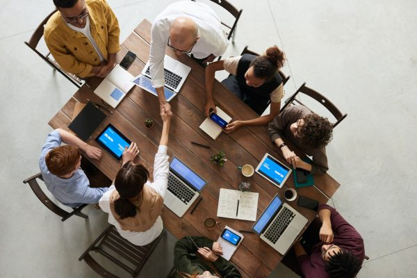 Overhead view of a group of people sit around a table at a meeting with laptops and notepads in front of them.
