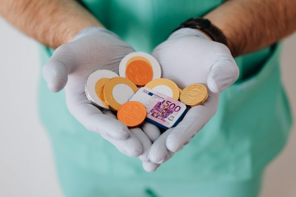 A medical professional in scrubs and gloves holds a handful of British coins.