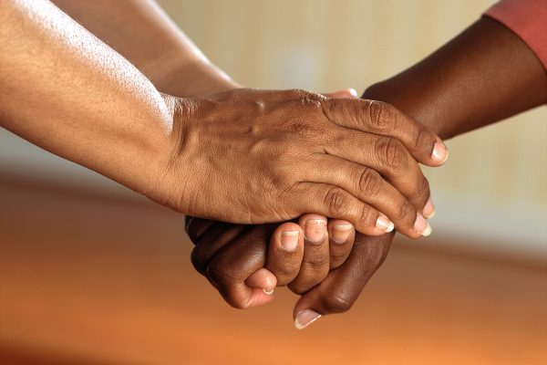 One pair of hands holds another hand in comfort.