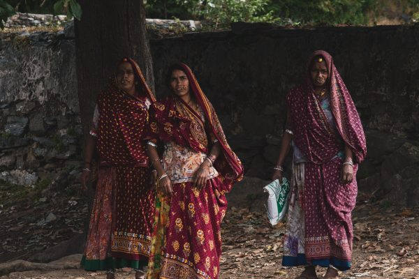 Three rural women walking together down a street in India.
