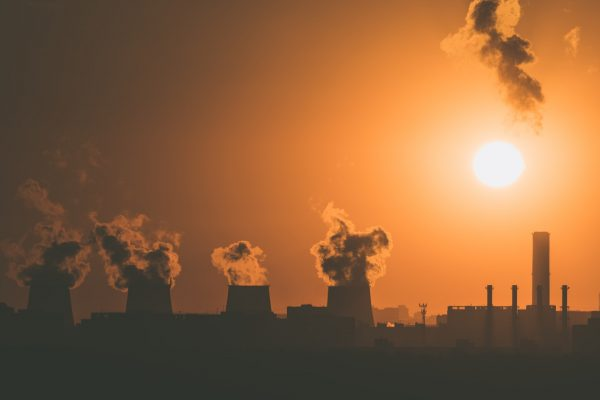 A factory emitting a smoke-like substance is silhouetted in a sunset.