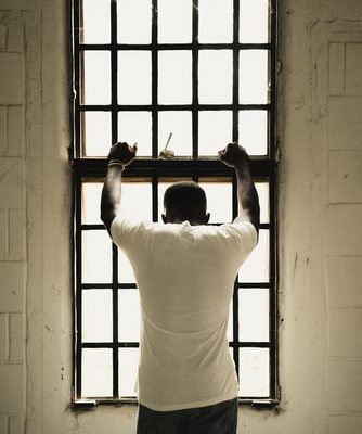 A person in a white shirt stands in front of a tall window with their back to the viewer and arms resting on the window.