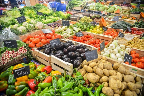 A variety of vegetables in crates being sold at a market.