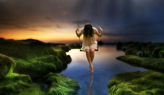 A girl sits on a swing looking down at the water below.
