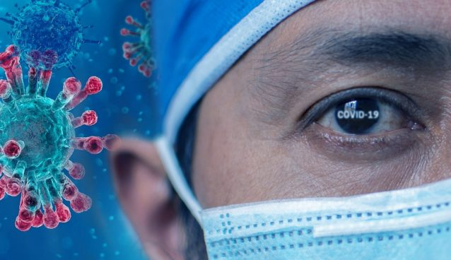 """A medical professional in a mask in of an illustration of the coronavirus, with """"COVID-19"""" typed onto the eye."""