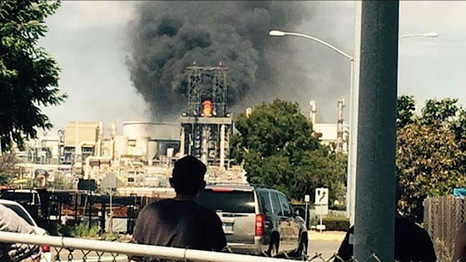 A person stands with their back to the camera watching a factory burn.