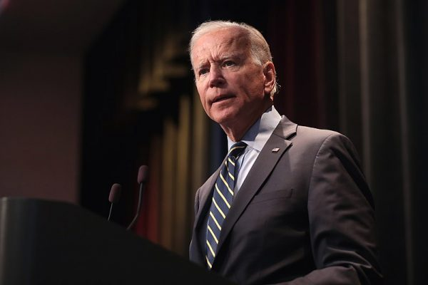 Joe Biden stands in front of a podium.